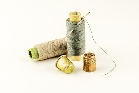 Two thimble for sewing and two spools of thread on a light background Stock Photo