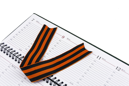 In an open diary sheet. Georges ribbon in the form of the letter V Stock Photo