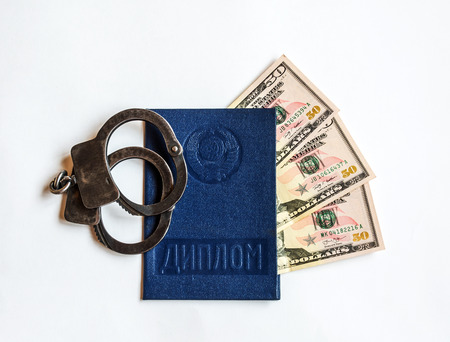On a light background is a diploma of education, handcuffs and banknotes