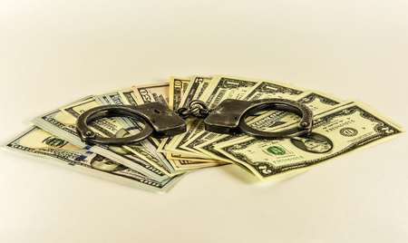 US dollars are covered with metal handcuffs