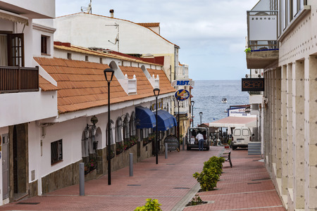 awnings windows: Spain, Tenerife - 10.09.2016: La Caleta village street leading to the shore of the ocean