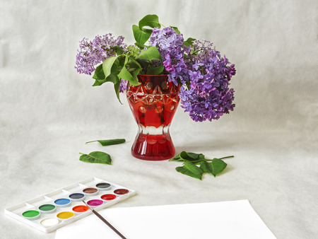 Lilac flowers in a red vase and watercolor paint Stock Photo