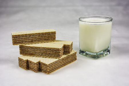 A glass of yogurt and wafers with chocolate filling on a gray background