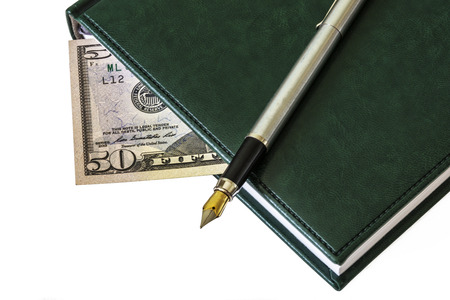 On the diary is a fountain pen. Between the sheets you see a bill of $ 50 Stock Photo