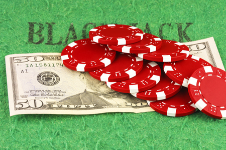On the green cloth of the poker table is a bill of $ 50 and ten red chips Stock Photo
