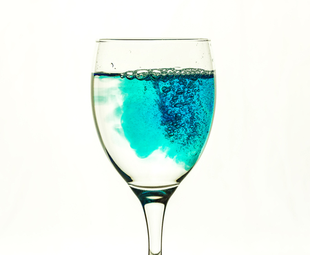 Blue liquid fills glass glass with transparent water