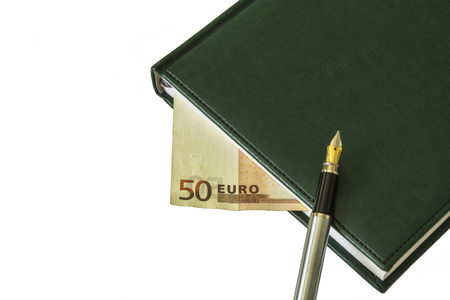 On the diary is a fountain pen. Between the sheets a bill of EUR 50 is visible Stock Photo