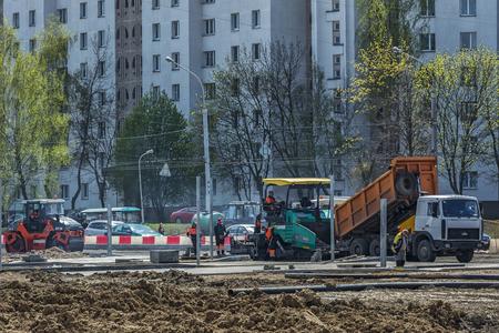 Belarus, Minsk - 06.05.2017: Dump truck, unloads asphalt into special equipment for paving asphalt Editorial