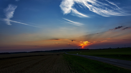Sunset in the field and the highway leading to the distance