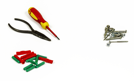 Screwdriver, pliers, screws and plastic dowels on a white background Stock Photo
