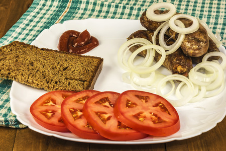 napkin ring: Rural food. Meat sausages with tomato, onion, sauce and bread