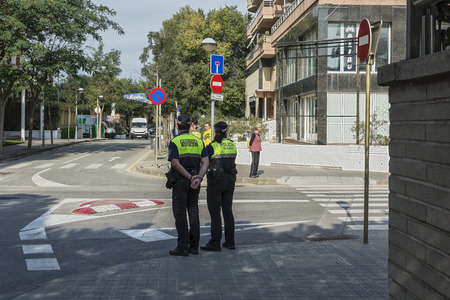 duty belt: Spain, Blanes - 09232017: Two policemen stand at the crossroads of the city street Editorial