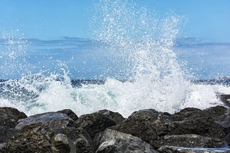 The tidal wave is broken into small splashes about the coastal stones