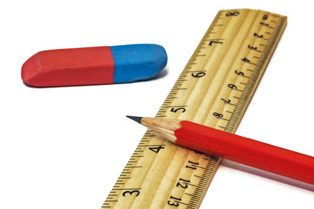 On a white background lie an eraser with a ruler and a simple pencil close-up