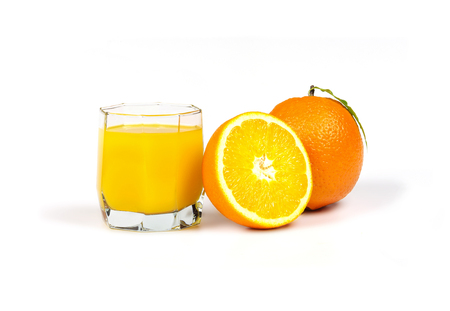 On white background there is a glass with freshly squeezed orange juice, lying next to a whole orange and half orange