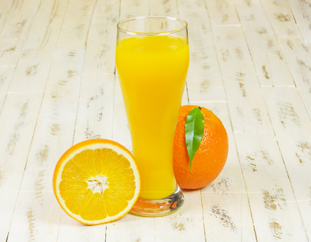 On the wooden surface stands a tall glass with freshly squeezed orange juice, lying next to a whole orange and half orange Stockfoto