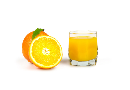 On white background there is a glass with freshly squeezed orange juice, lying next to a half of an orange and whole orange