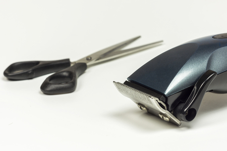 Hair clipper and scissors close up with blur elements on light background