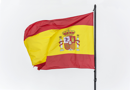 Spain flag on the flagpole on the bright background of the sky flutters in the wind Фото со стока