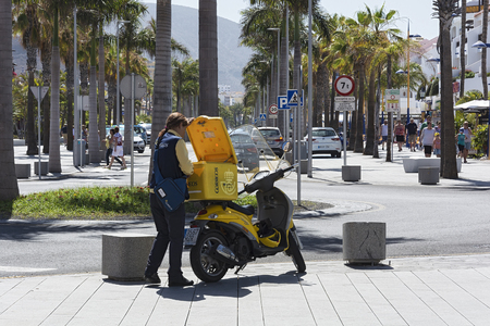 Spain, Tenerife - May 14, 2018: A postman girl stands near a yellow scooter on the sidewalk
