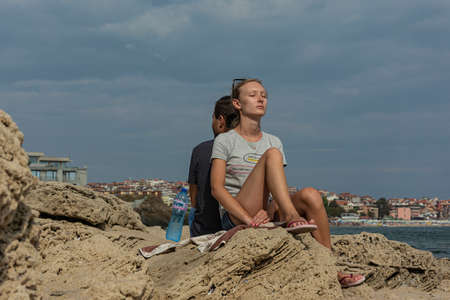 Bulgaria, Sozopol - 2018, 06 September: A girl sits with her back to a guy with her eyes closed, blurred background. Stock photo.