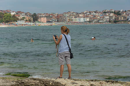Bulgaria, Sozopol - 2018, 06 September: A woman on the beach with a smartphone, blurred background. Stock photo.