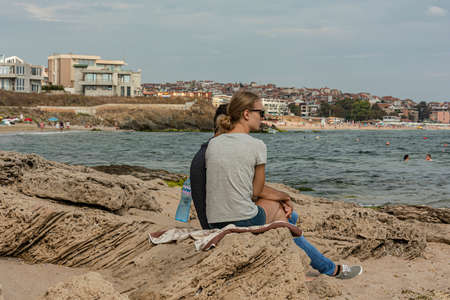 Bulgaria, Sozopol - 2018, 06 September: A girl with a guy sitting on the rocks near the sea, blurred background. Stock photo.
