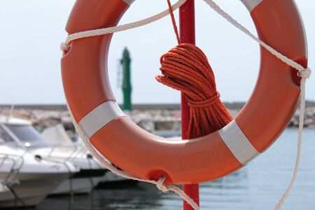 red lifebuoy in the foregroud with a small touristic port in the background