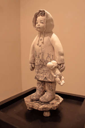 a majolica sculpture of a child with waterproof jacket under the rain keep in hands a teddy bear