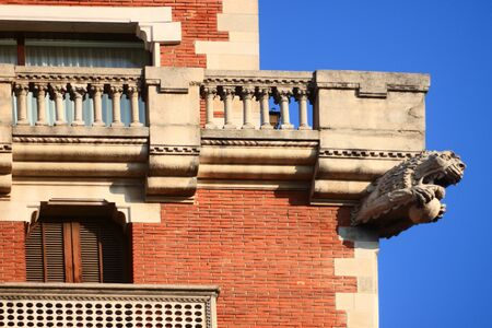 decorative gargoyle on the facade of a stately red brick building located in Milan