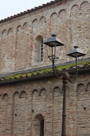 Retro-style street lampposts along a pedestrian street in the city of Acqui Terme, Italy.
