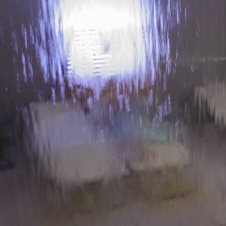 Amusing image of a woman sitted in a SPA seen through a wall of water. hires photo.