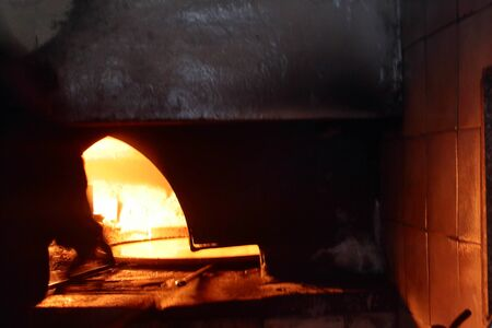 A pizzaiolo man cooks a chickpeas in a burning flame wood oven