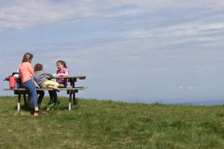 a family sitting on a bench in the mountains has picnics