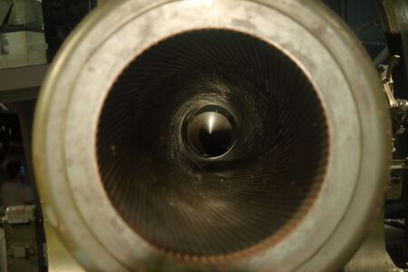 detail of the mouth of a large caliber ww2 cannon, the internal lining and the bullet at the bottom are clearly visible