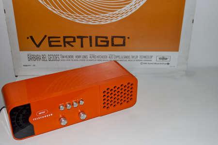 Vintage orange radio over vertigo movie poster mockup Sajtókép