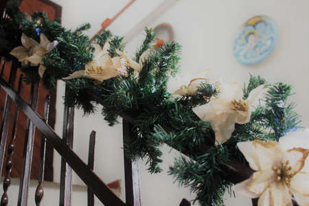flay a staircase in a private house decorated for Christmas with pine waving, lights and white flowers