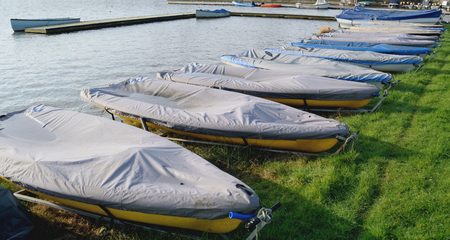 stored: Row of sailing boats stored next to the lake