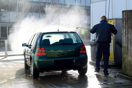washing car: Man washing car with high pressure spray Stock Photo