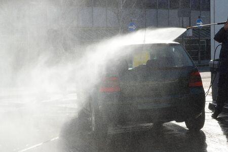 atmospheric pressure: Man washing car with high pressure spray Stock Photo