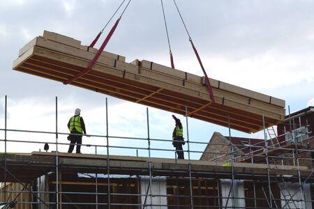 Bouwvakkers die groot houten kader op een nieuwe ontwikkelingplaats opheffen