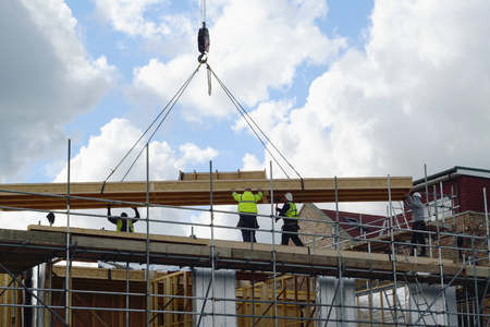 new development: Construction workers lifting big wooden frame on a new development site