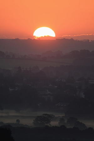 mistic: Sunrise on a misty morning over Axe Valley in East Devon, England