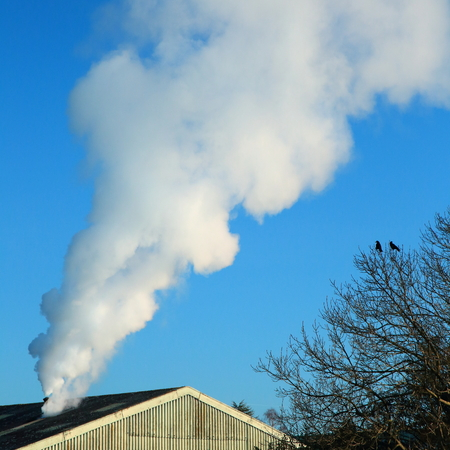 Smoke from factory against blue sky Stock Photo