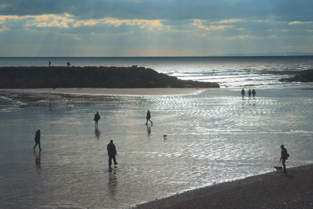Silhouettes of people walking on wet sandy beach in Sidmouth, Devon Stock Photo