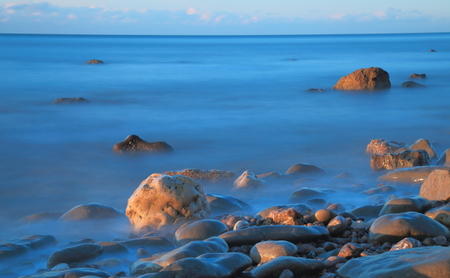 Blurred sea waves on a shingle beach in a morning near town of Seaton in Devon on the Jurassic Coast natural