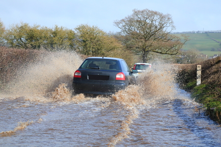 Car driving through a flooded road in East Devon Stock Photo