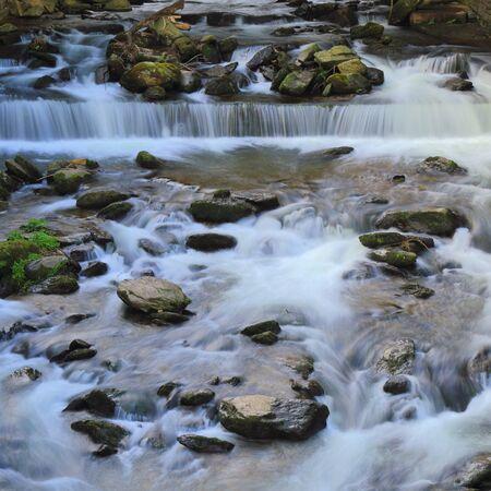 West Lyn River nel villaggio di Lynmouth, Devon, sul bordo settentrionale del Parco Nazionale di Exmoor. Lunga esposizione del fiume che scorre a valle.
