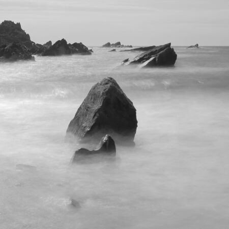 Rocks surrounded by blurred sea waves on th North Devon coast, England Stock fotó