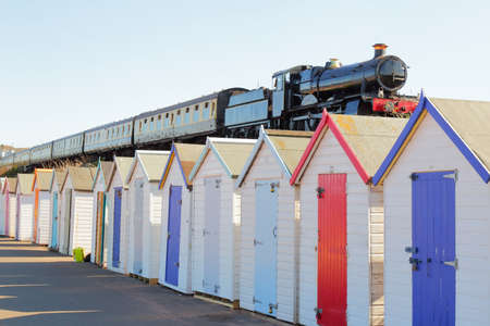 Train passing colorful beach huts in South Devon, UK